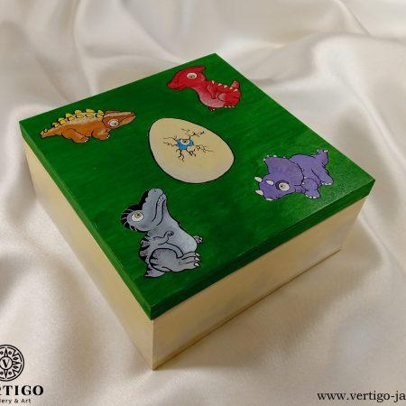Drewniane pudełko z małymi dinozaurami i jajkiem