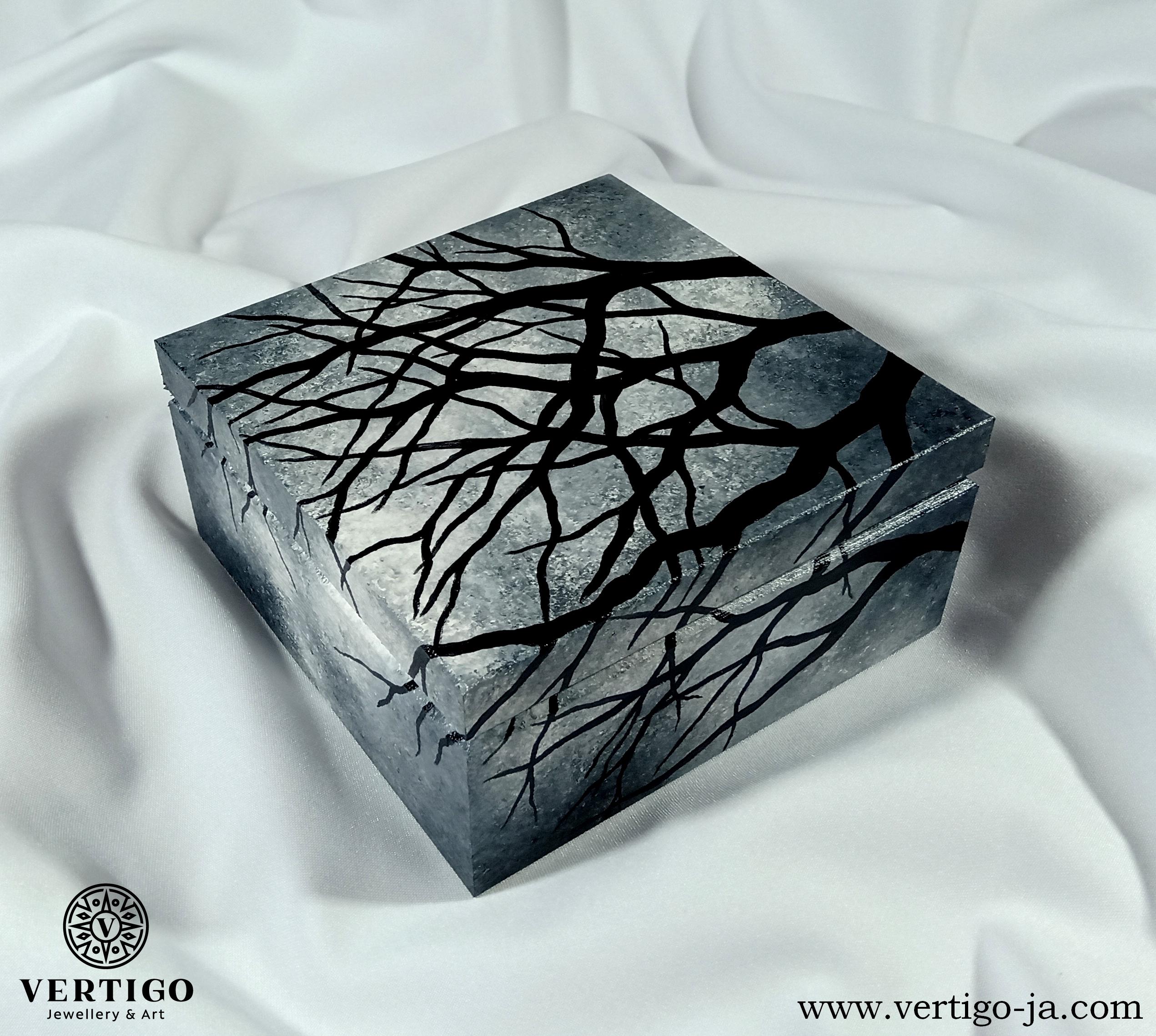 Drewniane pudełko z gałęziami na tle szarych chmur