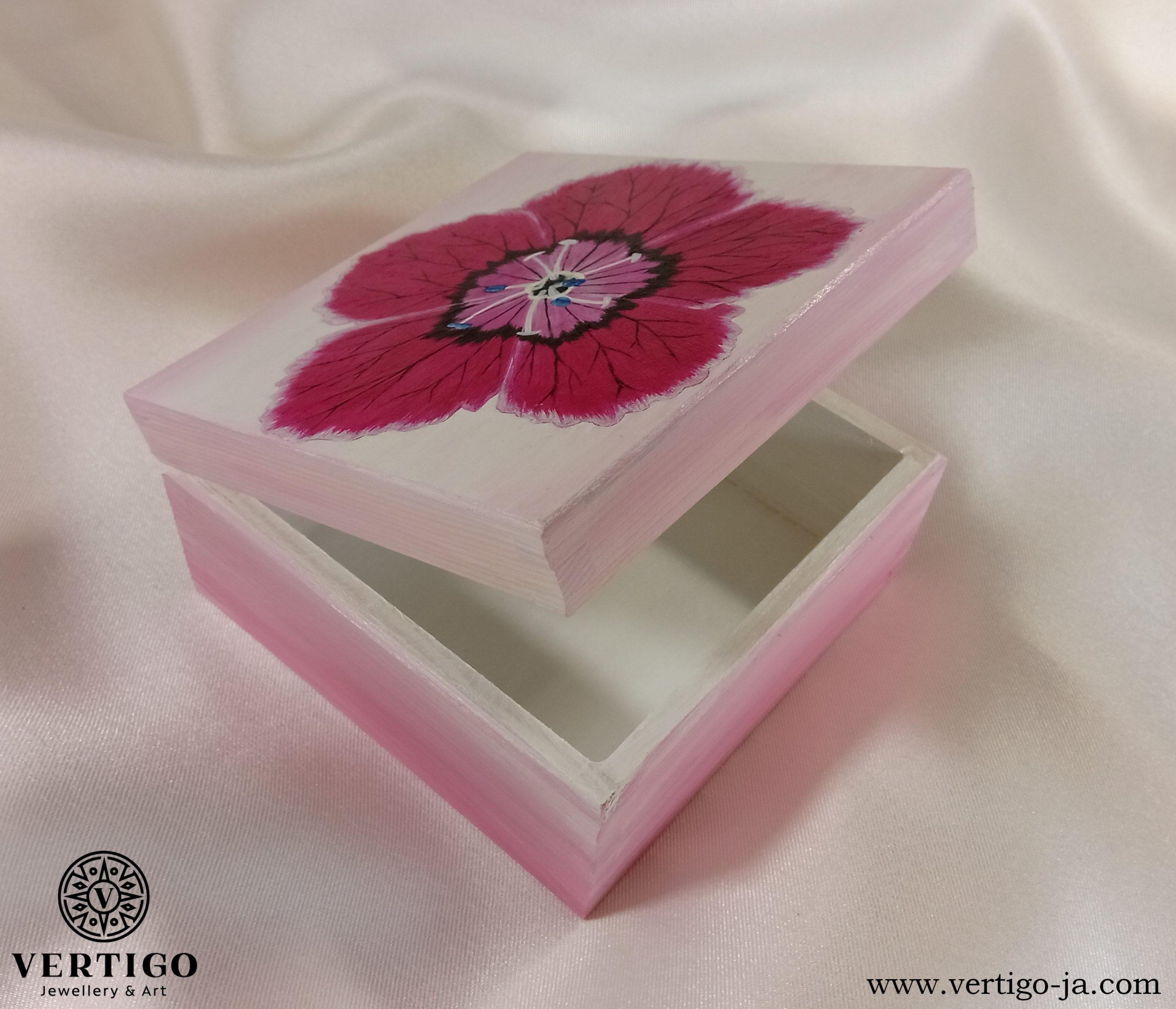Wnętrze drewnianego, różowego pudełka z goździkiem