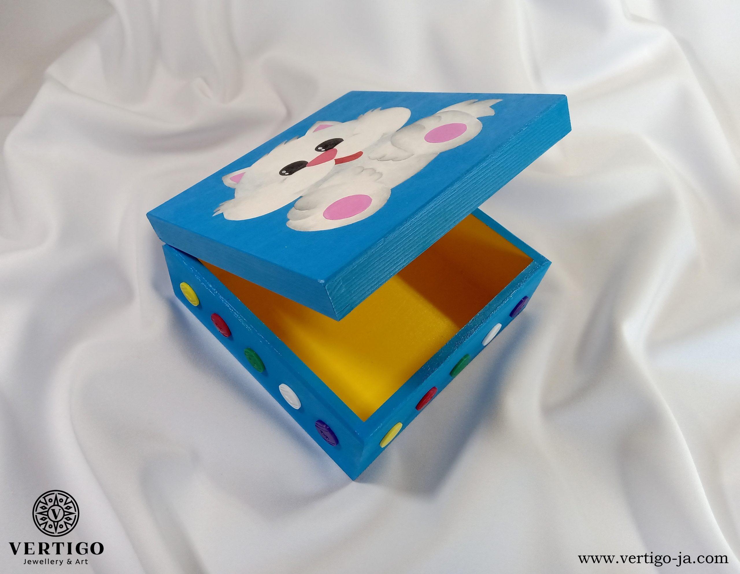 Wnętrze drewnianego, niebieskiego pudełka z białym kotkiem