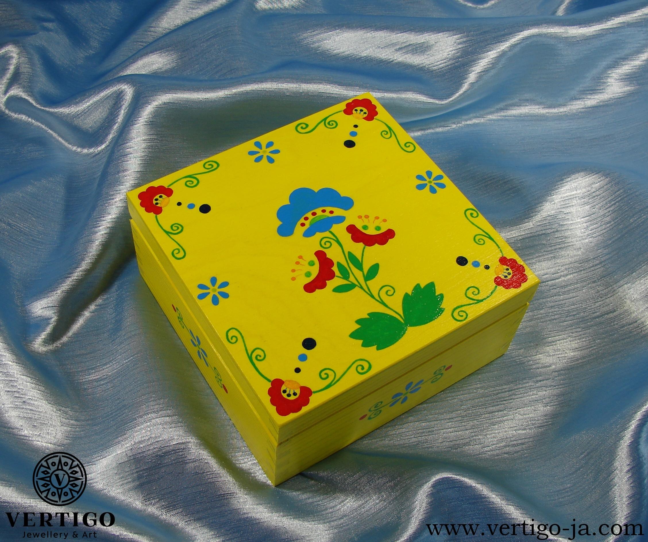 Drewniane, żółte pudełko z kolorowymi, ludowymi wzorami