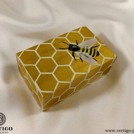 Drewniane pudełko z pszczołą na plastrze miodu