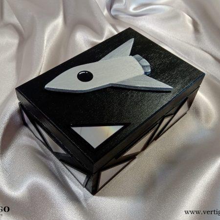 Drewniane pudełko z rakietą i błyszczącymi ozdobami