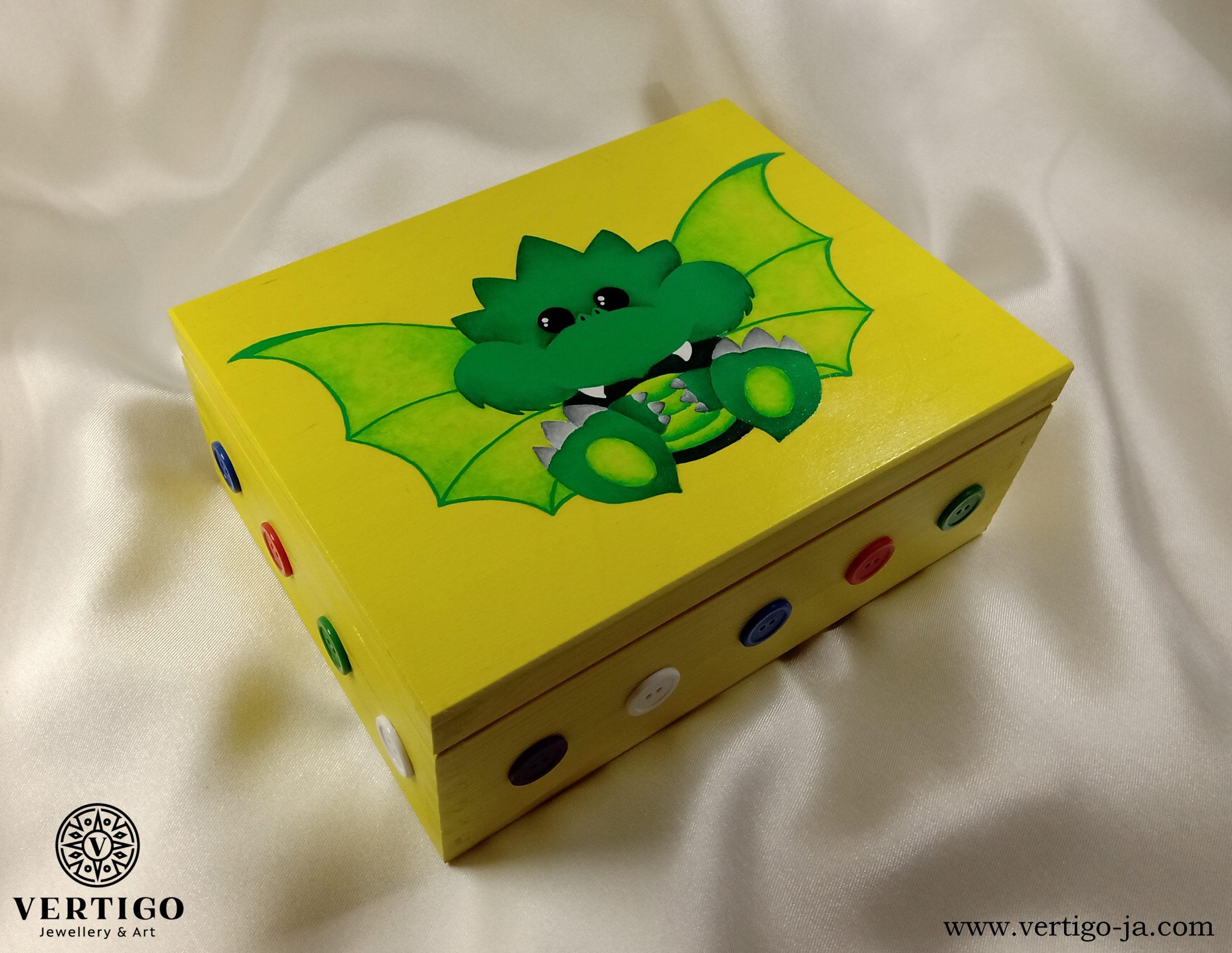 Drewniane, żółte pudełko z małym zielonym smokiem