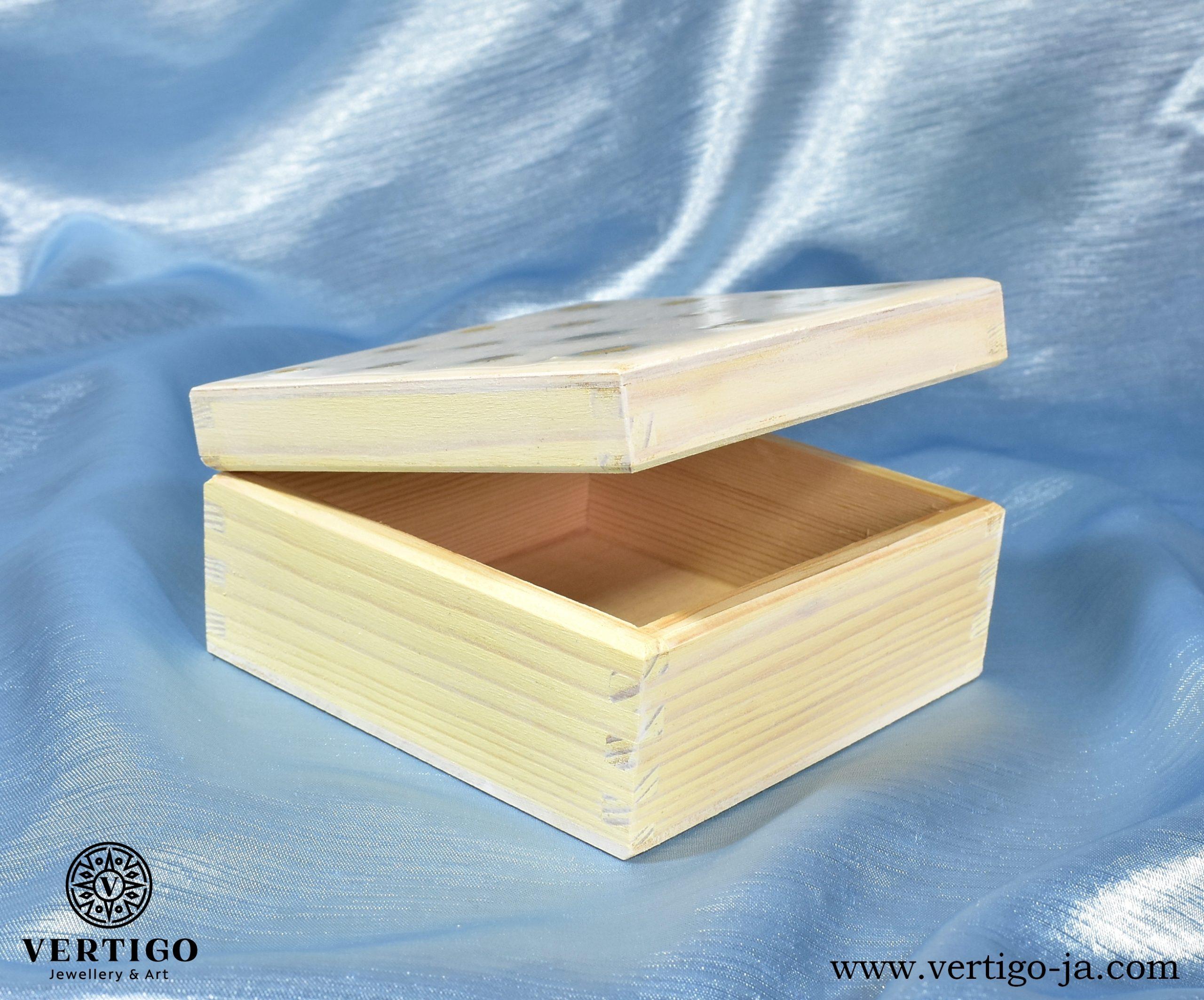 Środek białego, drewnianego pudełka ze stokrotkami w żywicy