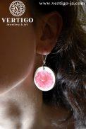 drewniane kolczyki z różowymi różami na uchu