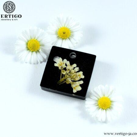 Kwadratowa zawieszka z żywicy z białymi kwiatkami na czarnym tle