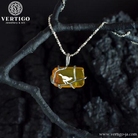 Srebrna zawieszka z bursztynem o nieregularnym kształcie z ozdobnym ptaszkiem na gałęzi