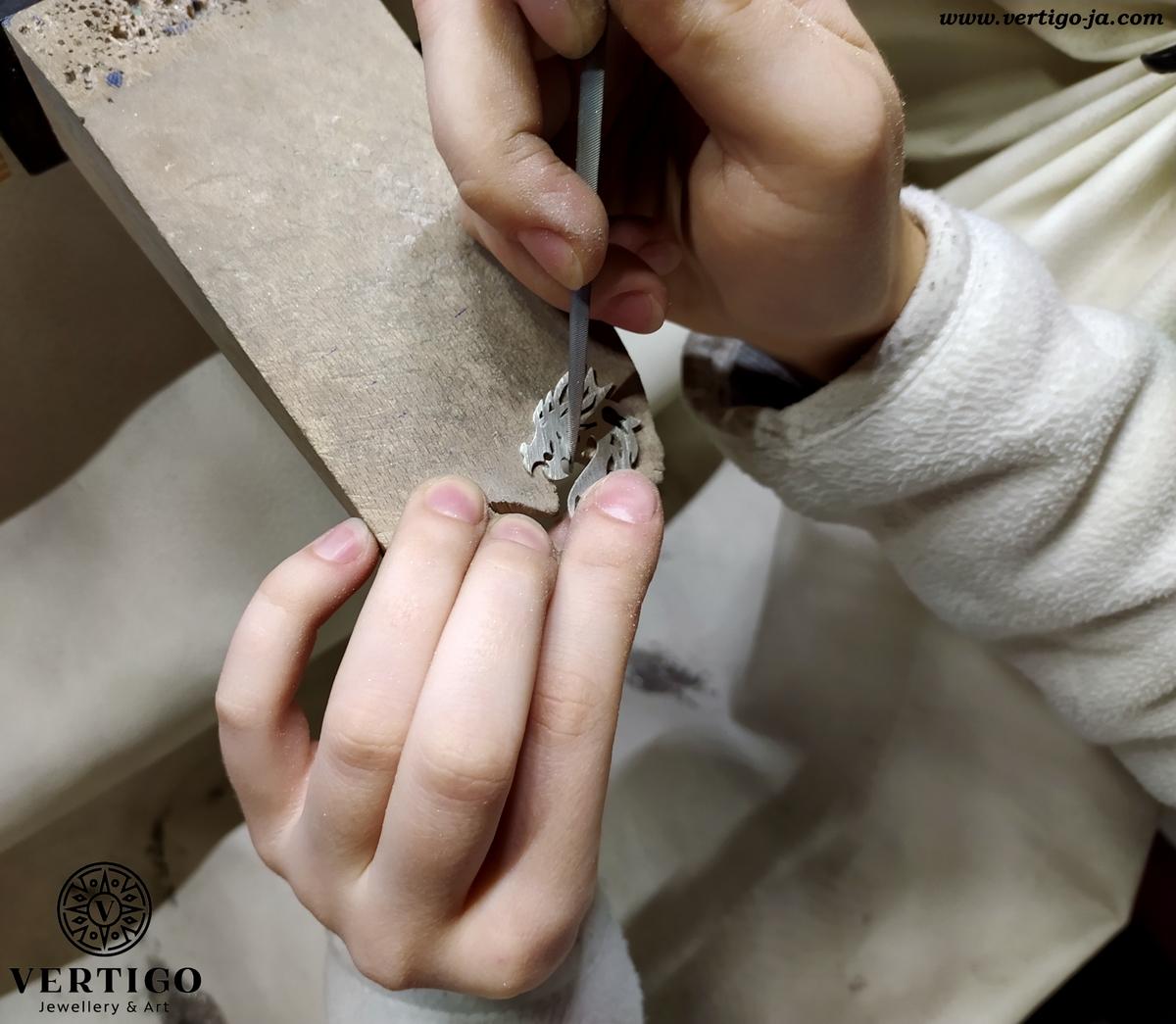 szlifowanie pilnikami srebrnej zawieszki ze smokiem