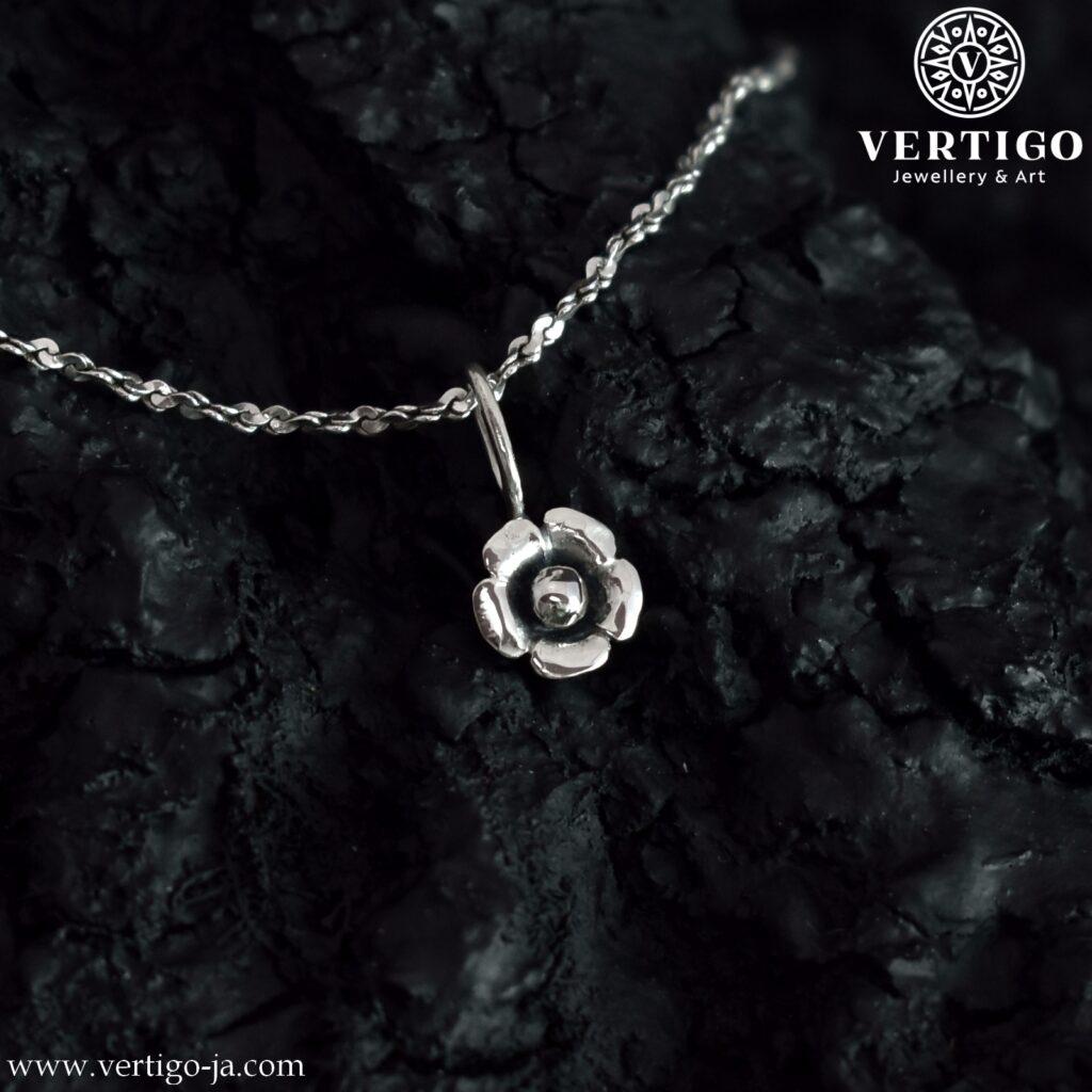 Mała zawieszka kwiatuszek wykonana z jasnego i oksydowanego srebra 0,925