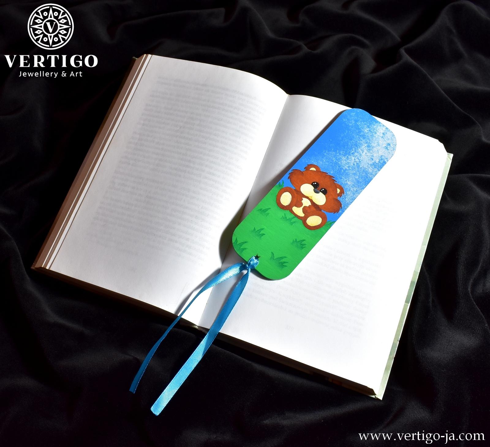 Ręcznie malowana zakładka do książki dla dzieci z brązowym misiem siedzącym na trawie pod błękitnym niebem. Drewniana.