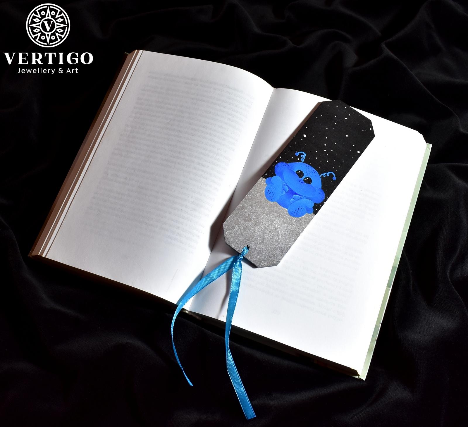 Drewniana zakładka do książki dla dzieci z uroczym ufoludkiem siedzącym na komecie na tle czarnego nieba z gwiazdami.