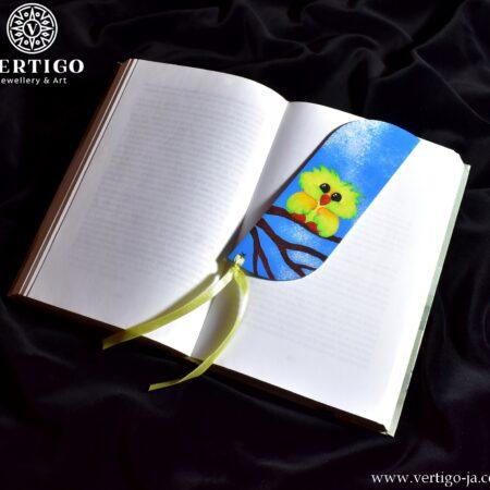 Drewniana zakładka do książki dla dzieci z kolorowym ptaszkiem na gałęzi, w tle niebieskie niebo. Żółta wstążka.