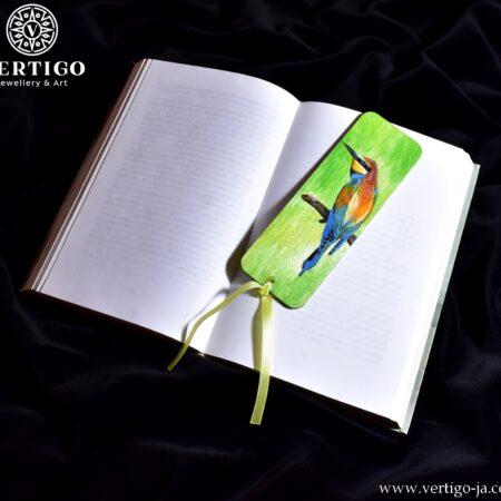 Drewniana, ręcznie malowana zakładka do książki z kolorowym ptakiem - żołną. Zielone tło. Żółta wstążka.