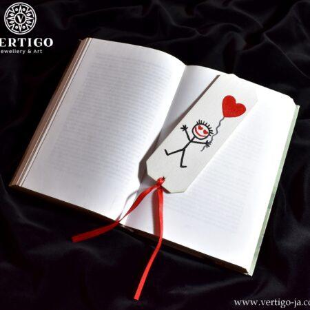 Biała, drewniana zakładka do książki z zakochanym kreskowym ludzikiem trzymającym czerwony balon - serduszko.