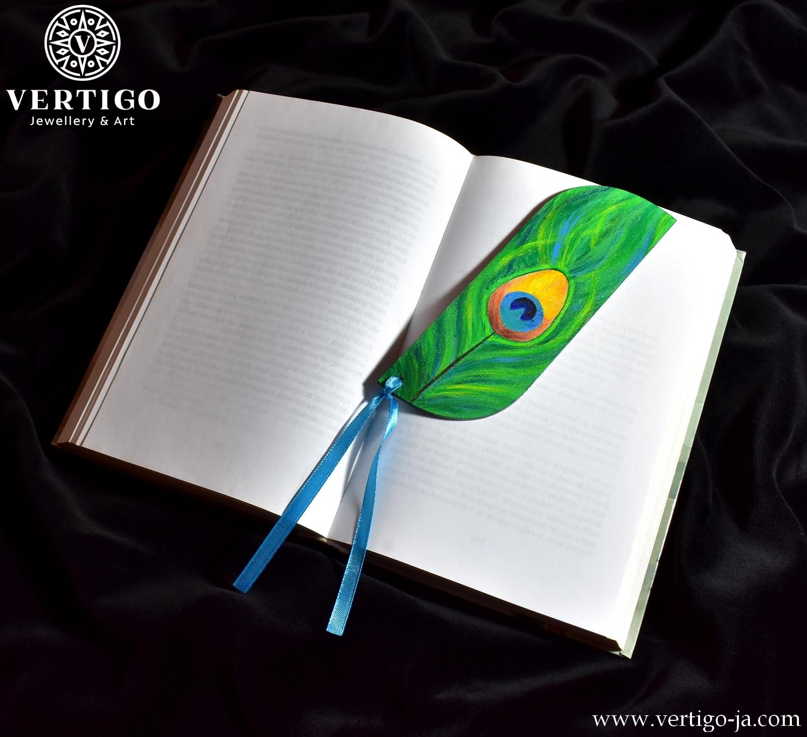 Ręcznie malowana zakładka do książki z pawim piórem. Do zakładki przywiązano niebieska wstążkę. Drewniana zakładka.