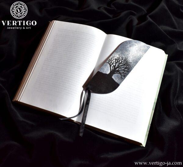 Drewniana zakładka do książki z samotnym czarnym drzewem na tle szarego, pochmurnego nieba. Czarna wstążka.