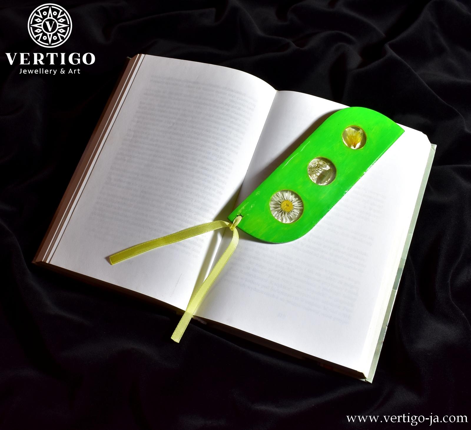 Zielona, drewniana zakładka z 3 otworami z zatopionymi w żywicy listami i kwiatami. Żółta wstążka.