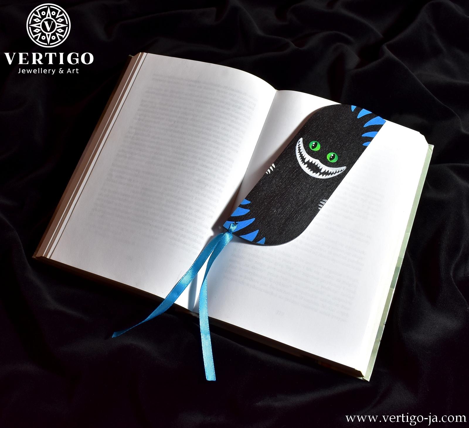 Drewniana zakładka do książki z ręcznie malowanym znikającym kotem na czarnym tle - widoczne zęby, oczy i niebieskie pasy kota
