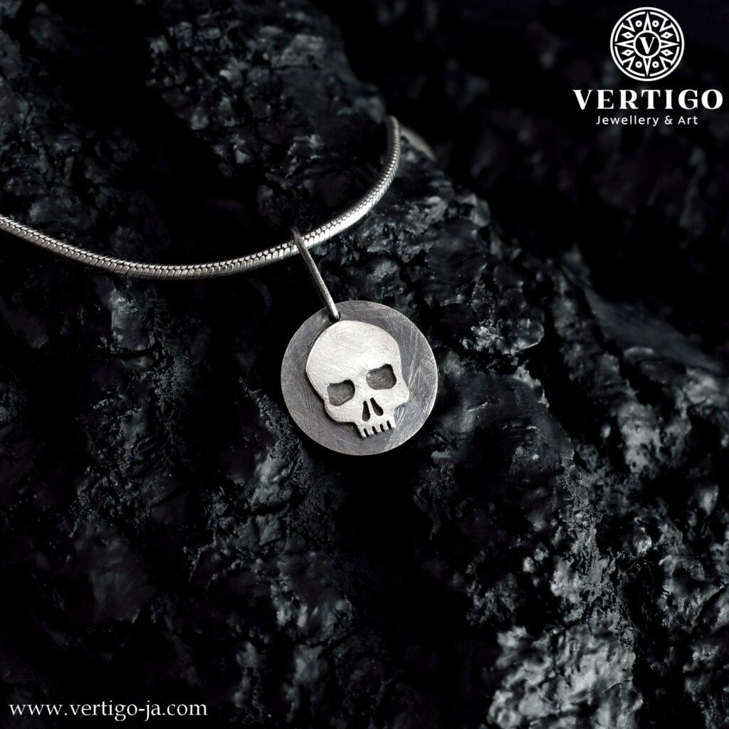 Okrągła, częściowo oksydowana zawieszka ze srebra z czaszką. Surowo wyglądająca faktura. Jasna czaszka na ciemnym tle.