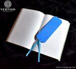 Niebieski tył drewnianej zakładki z ludowymi wzorami. Zakładka zakończona niebieską wstążką.