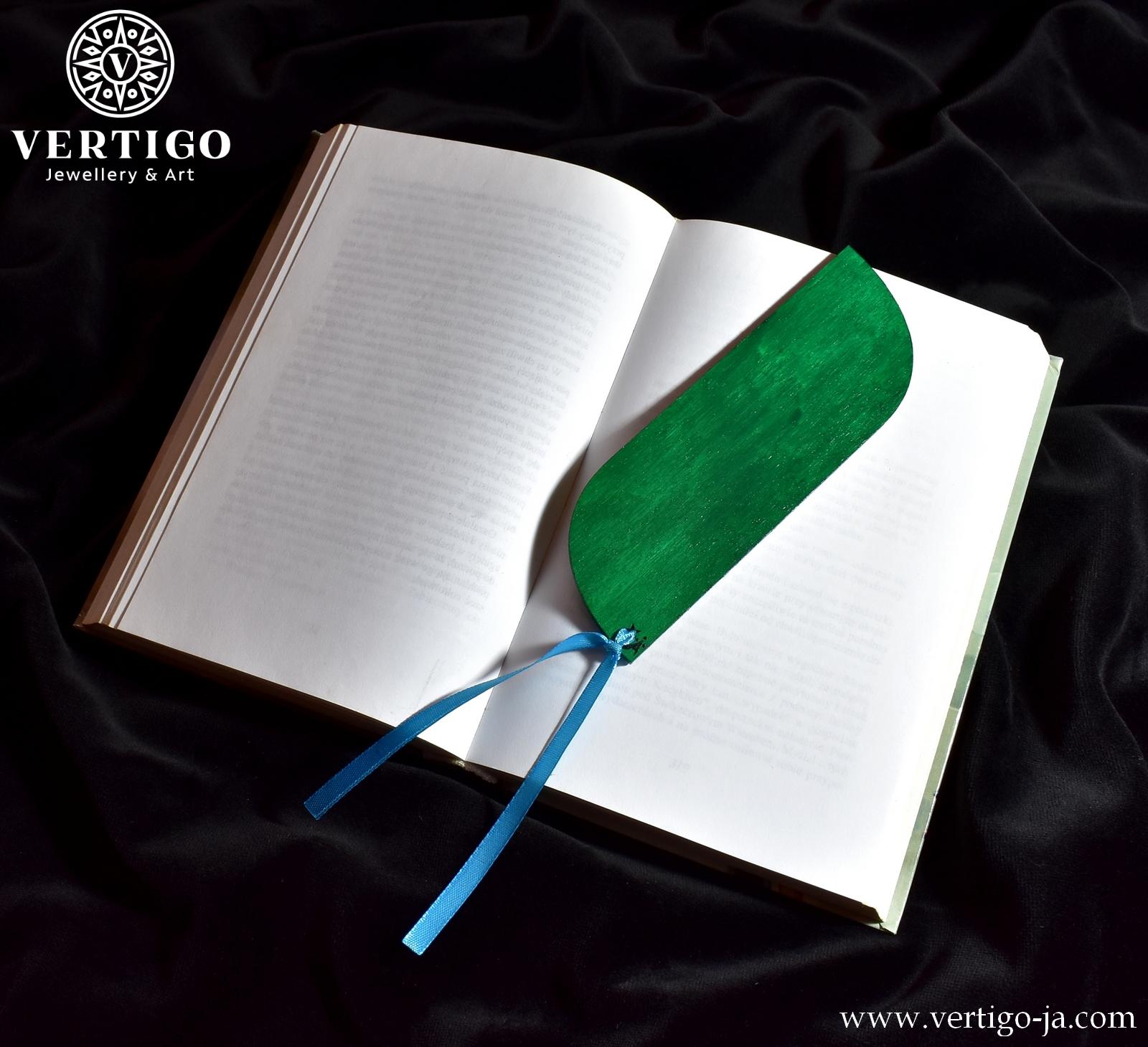 Tył drewnianej zakładki do książki z pawim piórem. Zielony kolor. Zakończona niebieska wstążką.