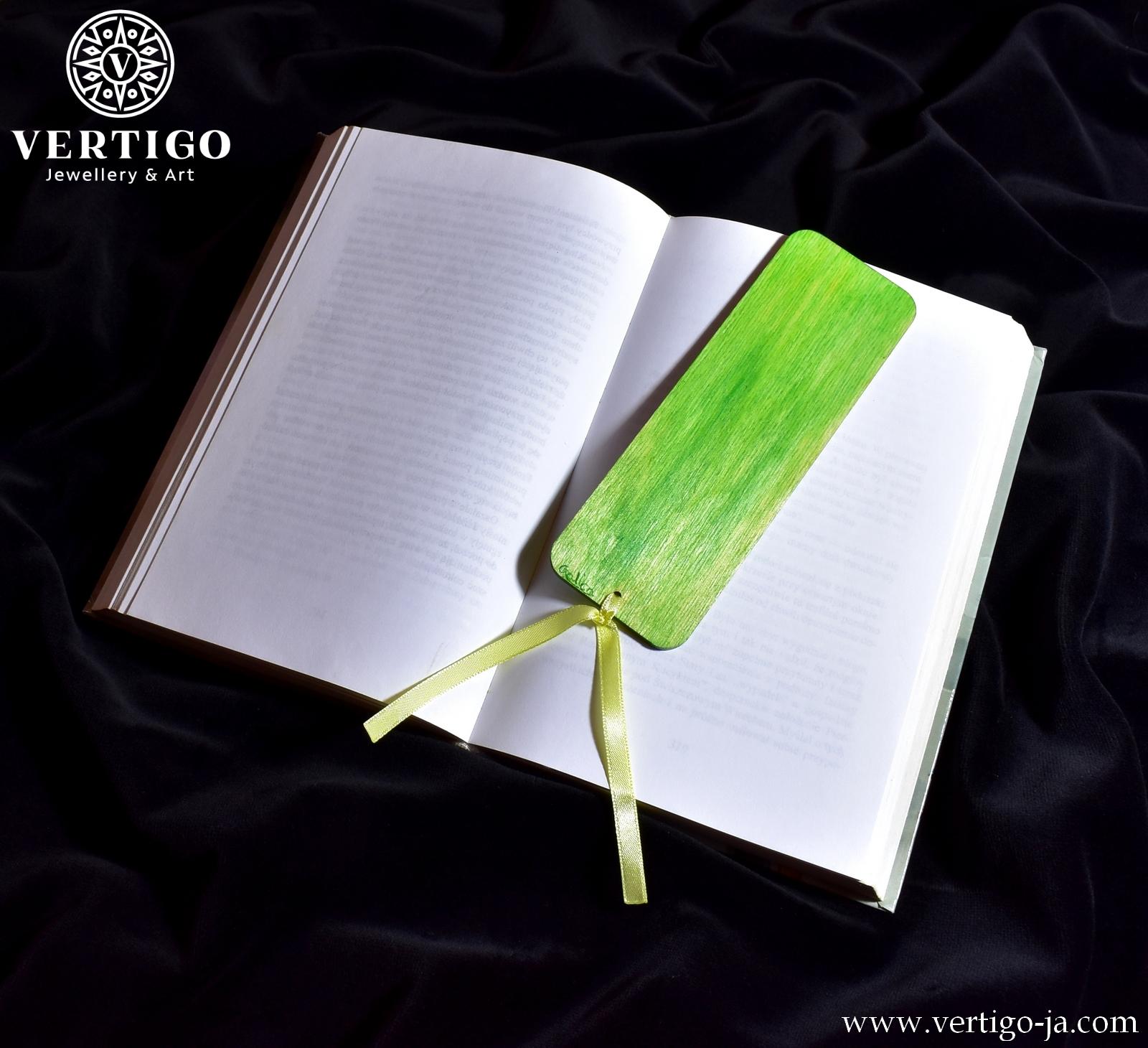 Zielony tył drewnianej zakładki do książki z kolorowym ptakiem żołną