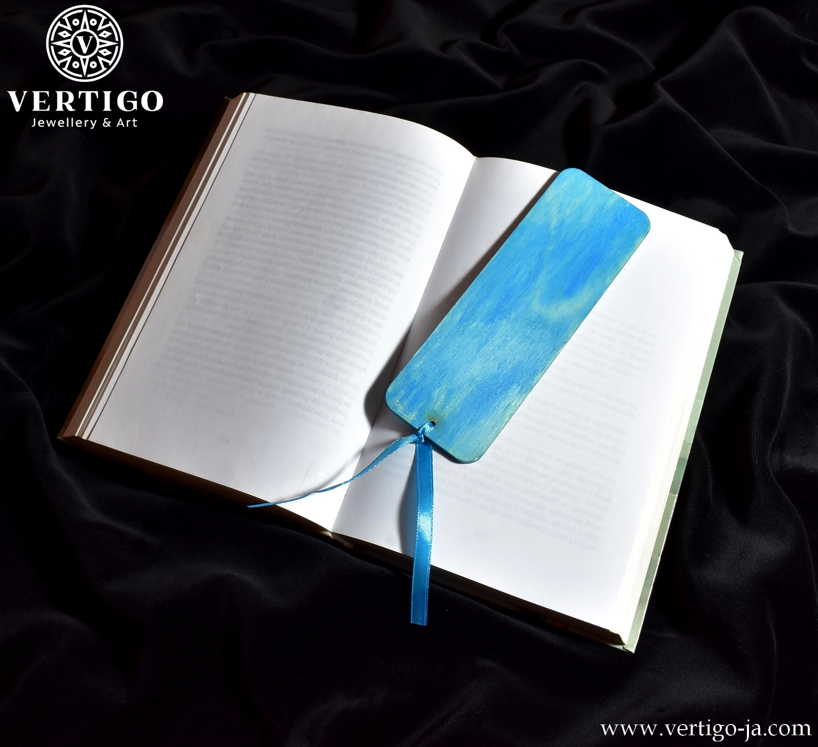 Niebieski tył drewnianej zakładki do książki z biało-czerwoną różą. Niebieska wstążka