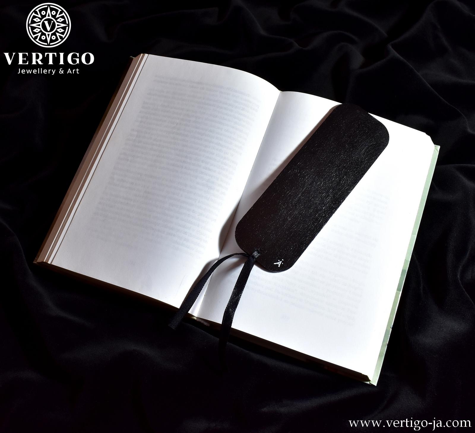 czarny tył drewnianej zakładki do książki z czarnym tatuażowym smokiem na białym tle. Czarna wstążka.
