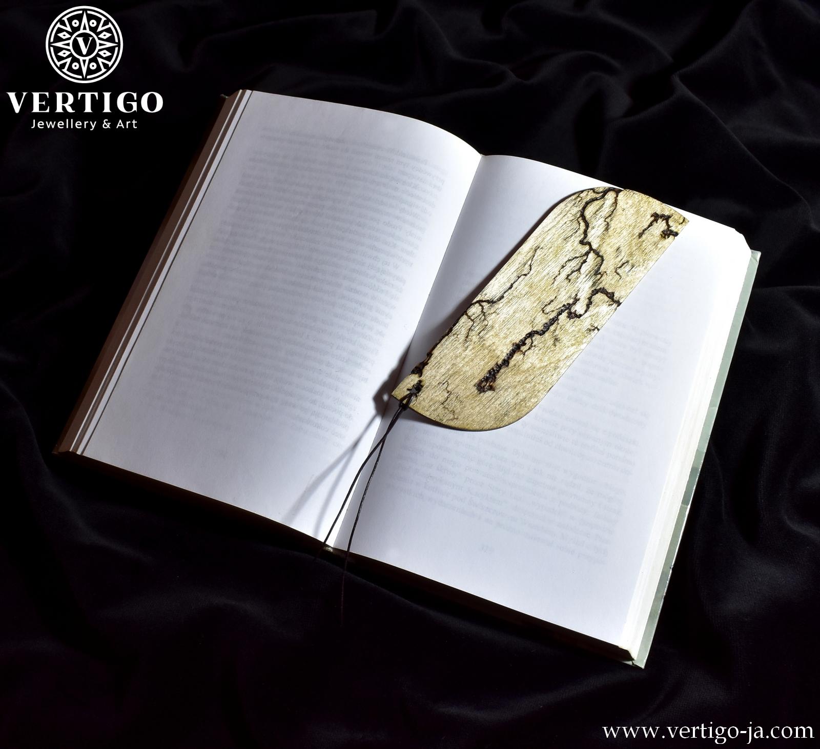 Tył drewnianej zakładki wypalanej metodą Lichtenberga - dwa zaokrąglone rogi. Ciemnobrązowy skórzany rzemyk jako wykończenie.