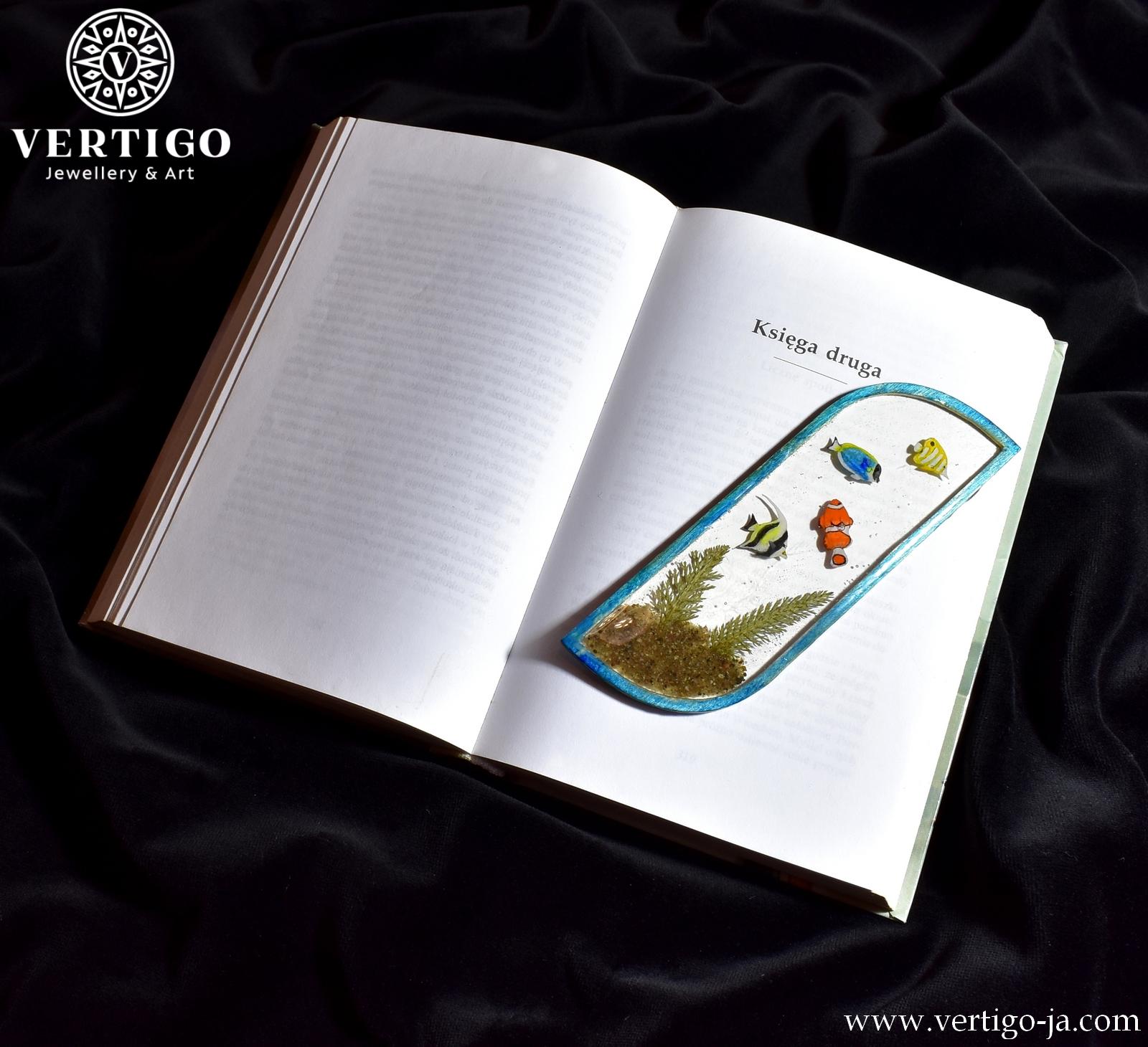 Tył zakładki do książki z żywicy z 4 rybkami, piaskiem i 2 zielonymi roślinkami. Niebieska ramka z drewna wypełniona żywicą.