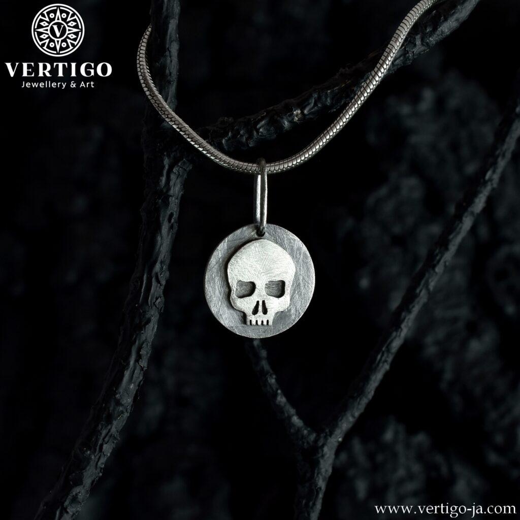 Srebrna zawieszka z czaszką. Jasna czaszka na okrągłym, ciemnym tle. Fakturowana powierzchnia.