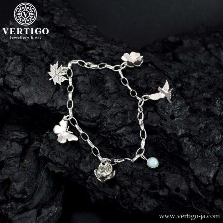 Srebrna bransoletka z 6 zawieszkami: amazonit, ptaszek, koniczynka, liść, motyl, kwiatek. Łańcuszek o szerokich oczkach.