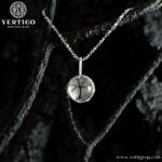 Srebrny wisiorek z kryształem górskim - okrągły kryształ górski przez który widać wycięte w srebrze drzewo